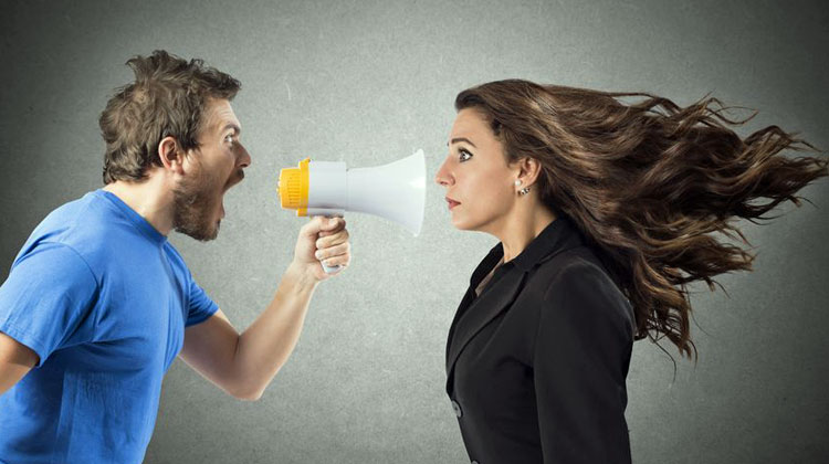 man shouting at woman through megaphone